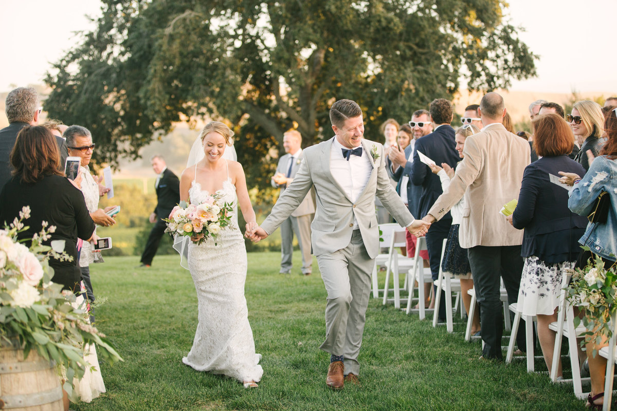 Bride and groom walk down aisle after ceremony at Firestone Vineyard