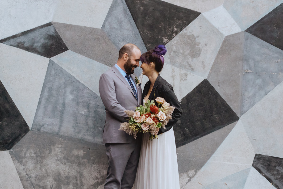 bride and groom laughing in front of mural