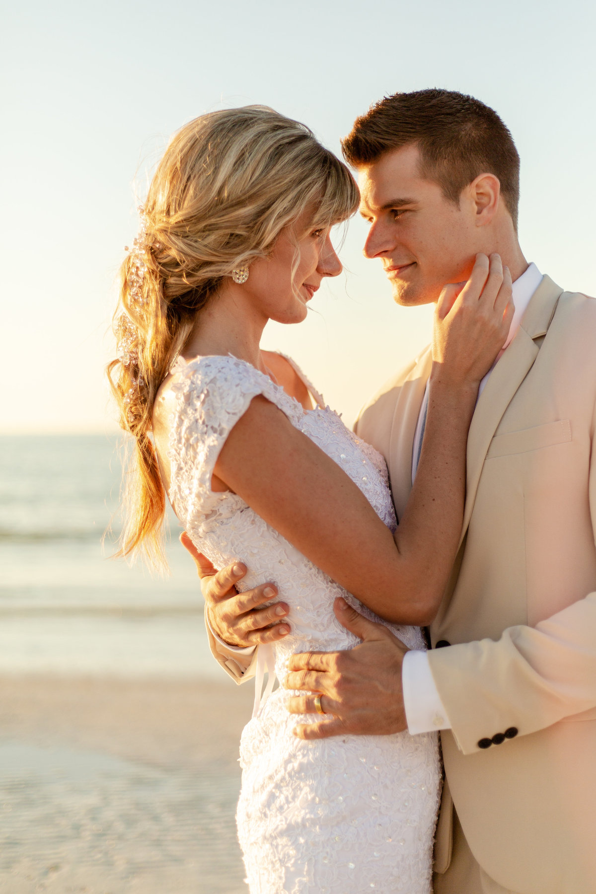 Bride and groom smile at each other on their wedding day at the beach in Dunedin, Florida at sunset with golden hour glow