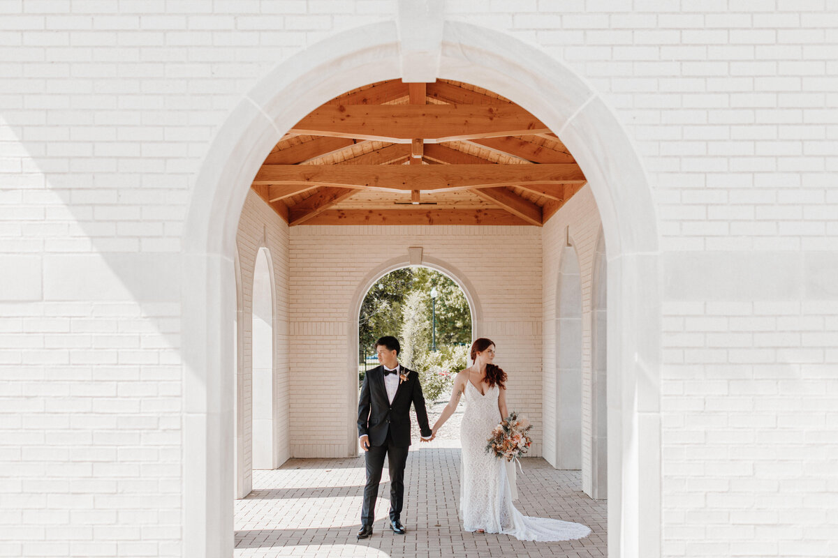 Bride and groom holding hands standing under the roof of a church building