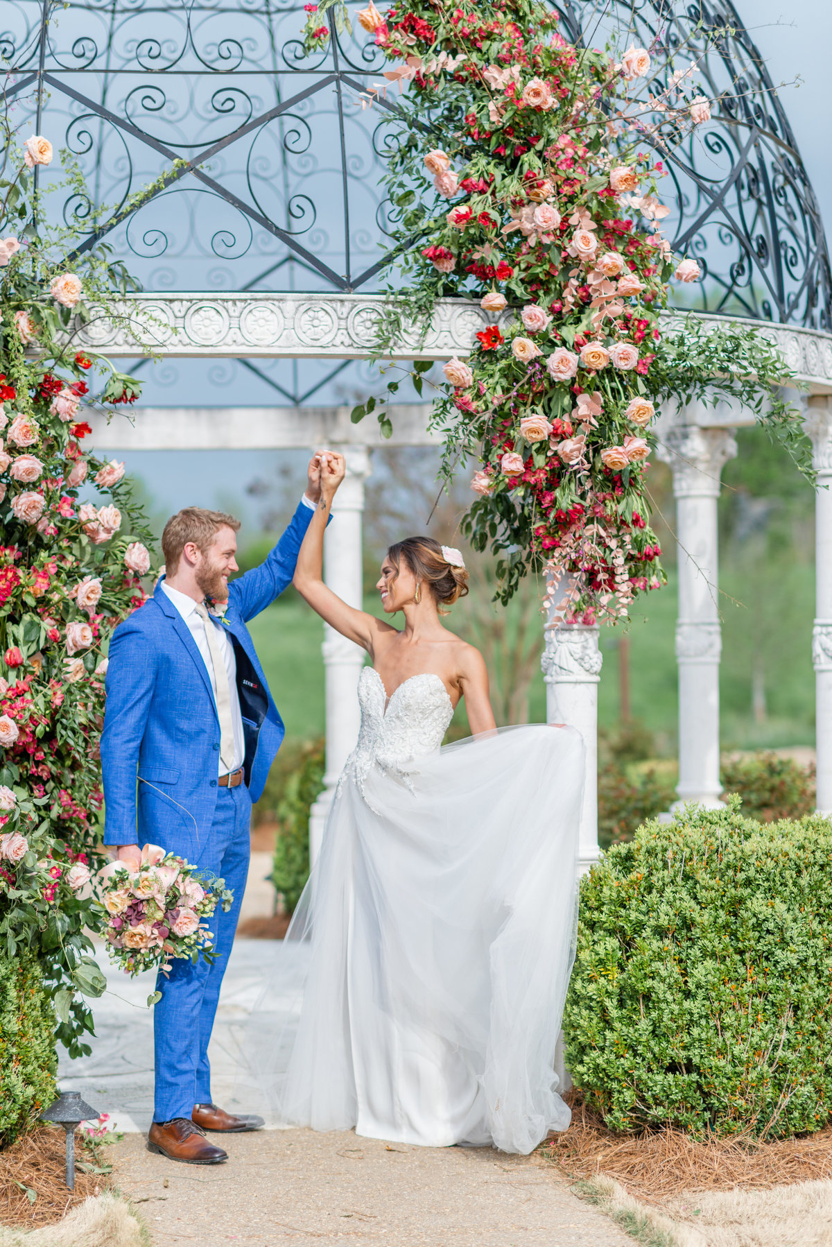 Groom in blue suit holds bouquet while twirling bide in front of Italian gazebo
