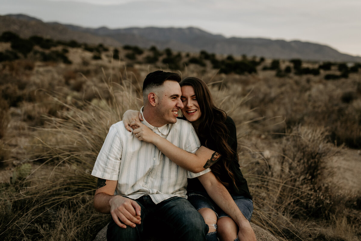engaged couple sitting and hugging in the desert