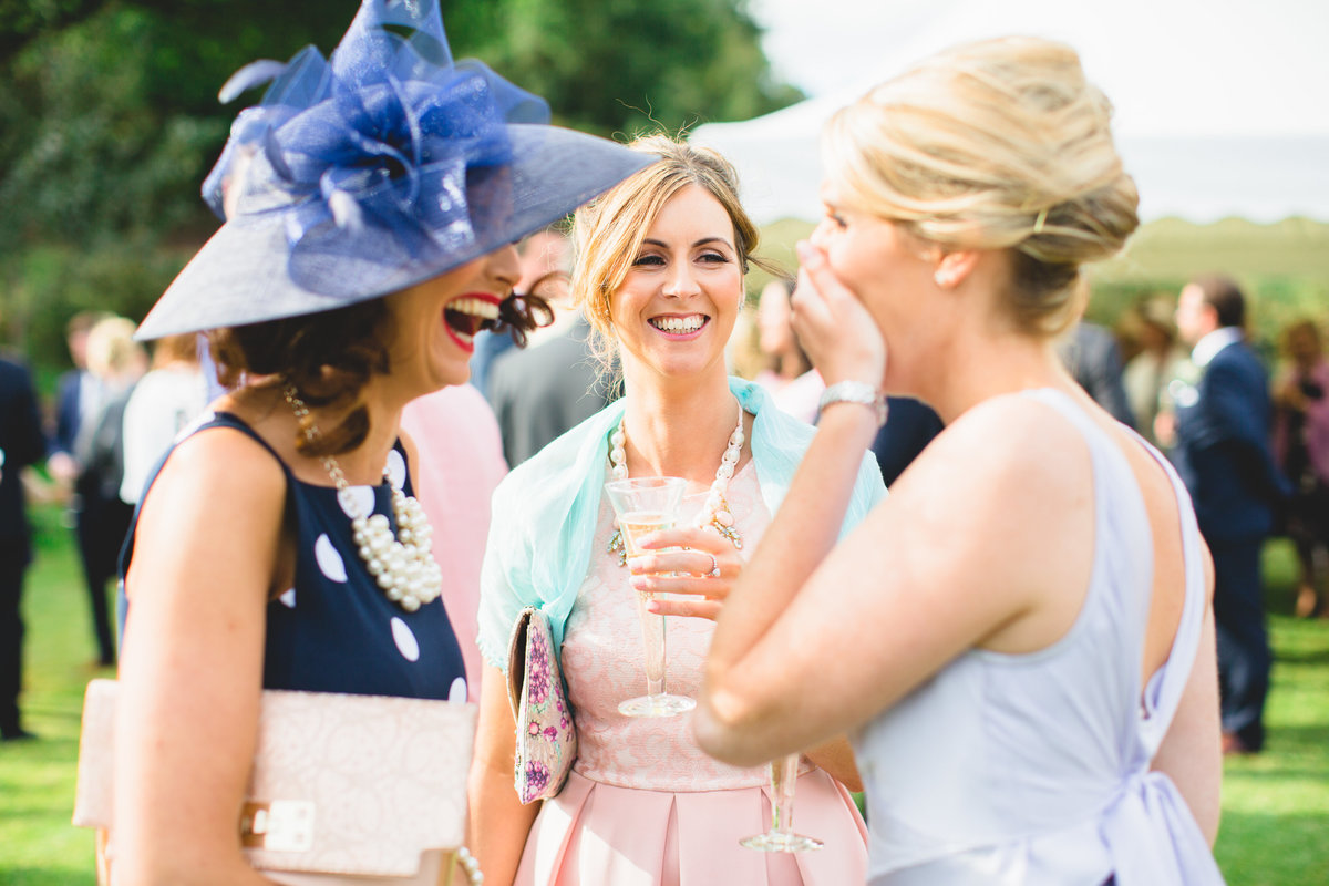 outdoor wedding photos of wedding guests laughing and talking with champagne