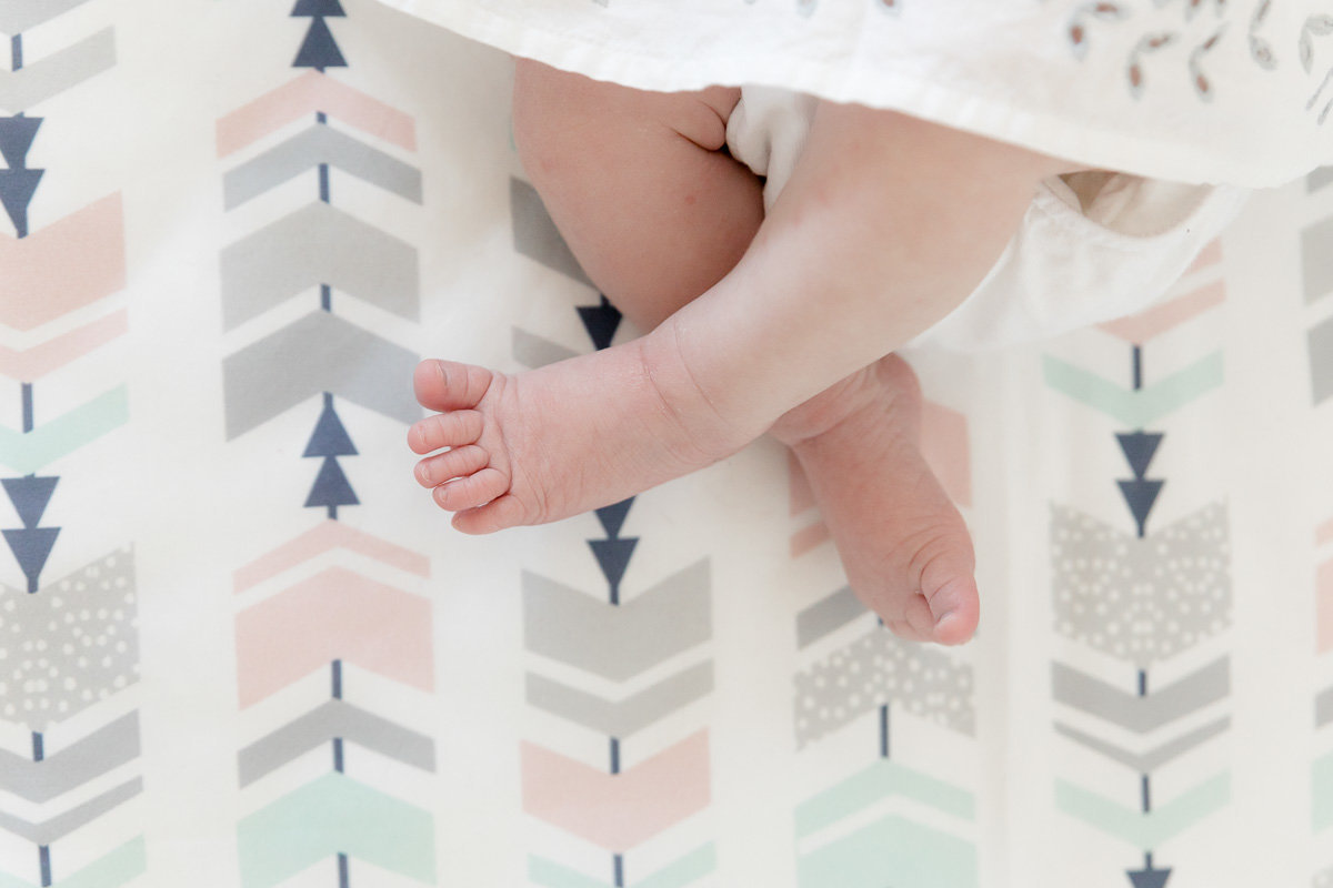 Baby feet in the crib on chevron sheets