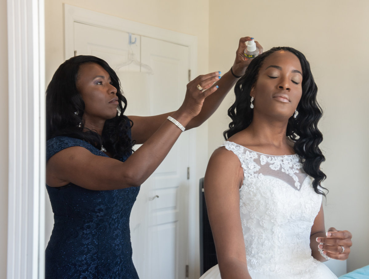 Mother putting the finishing touches on the brides hair