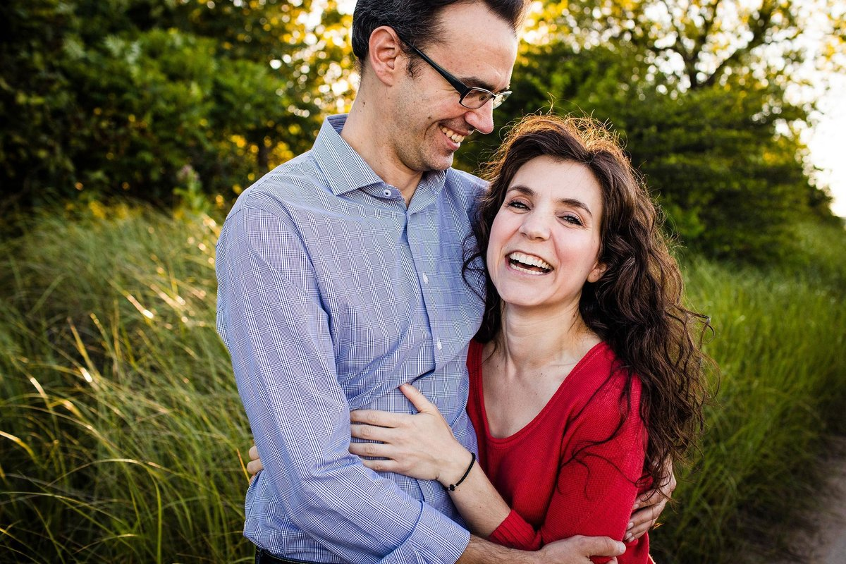 A couple laughs together during a Montrose Harbor engagement session.