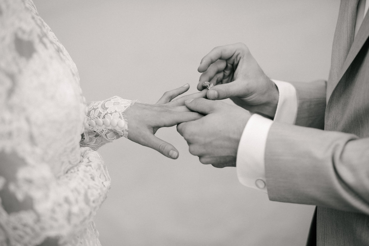 Close up of groom placing wedding ring on  bride's ring finger, in black and white