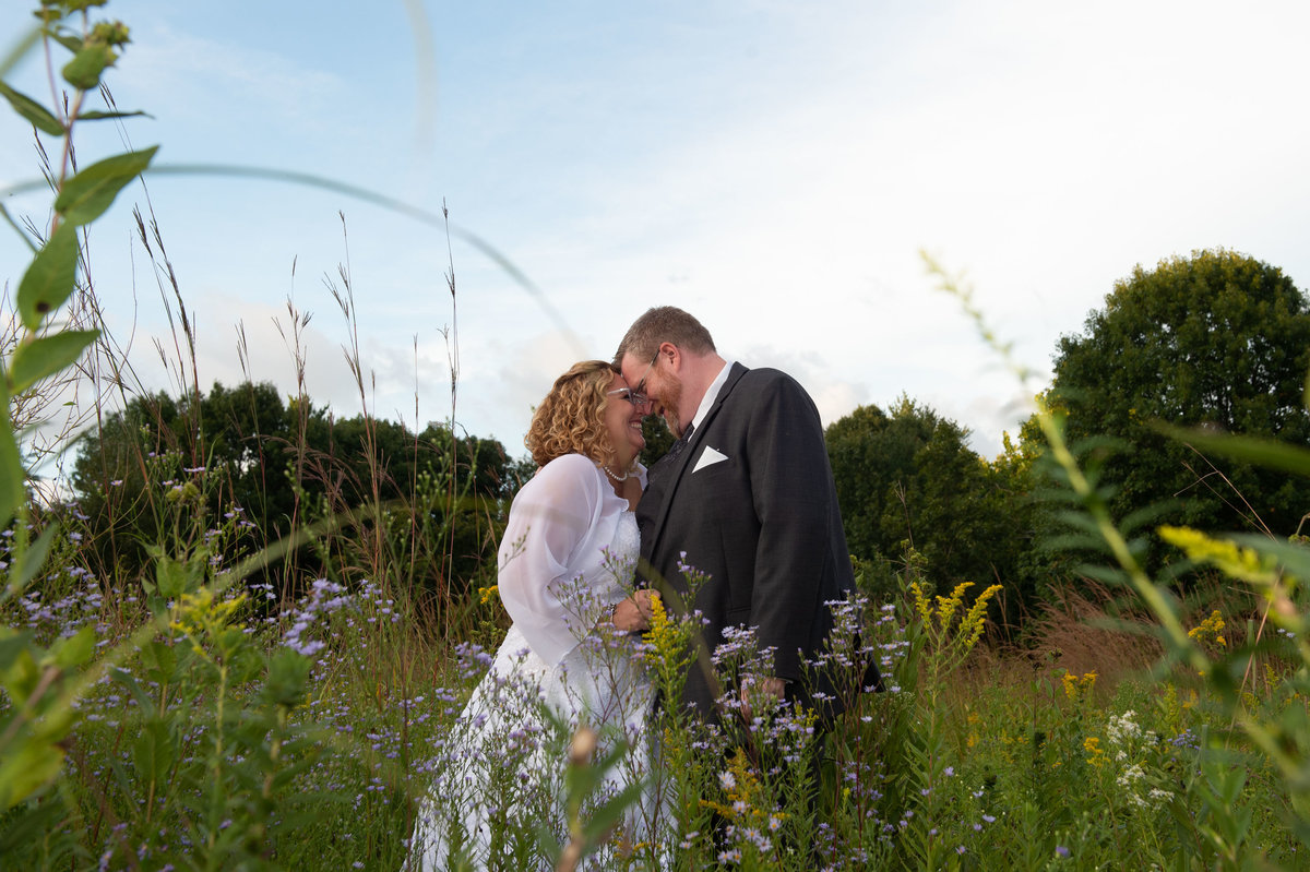 bride and groom in field of wildflowers