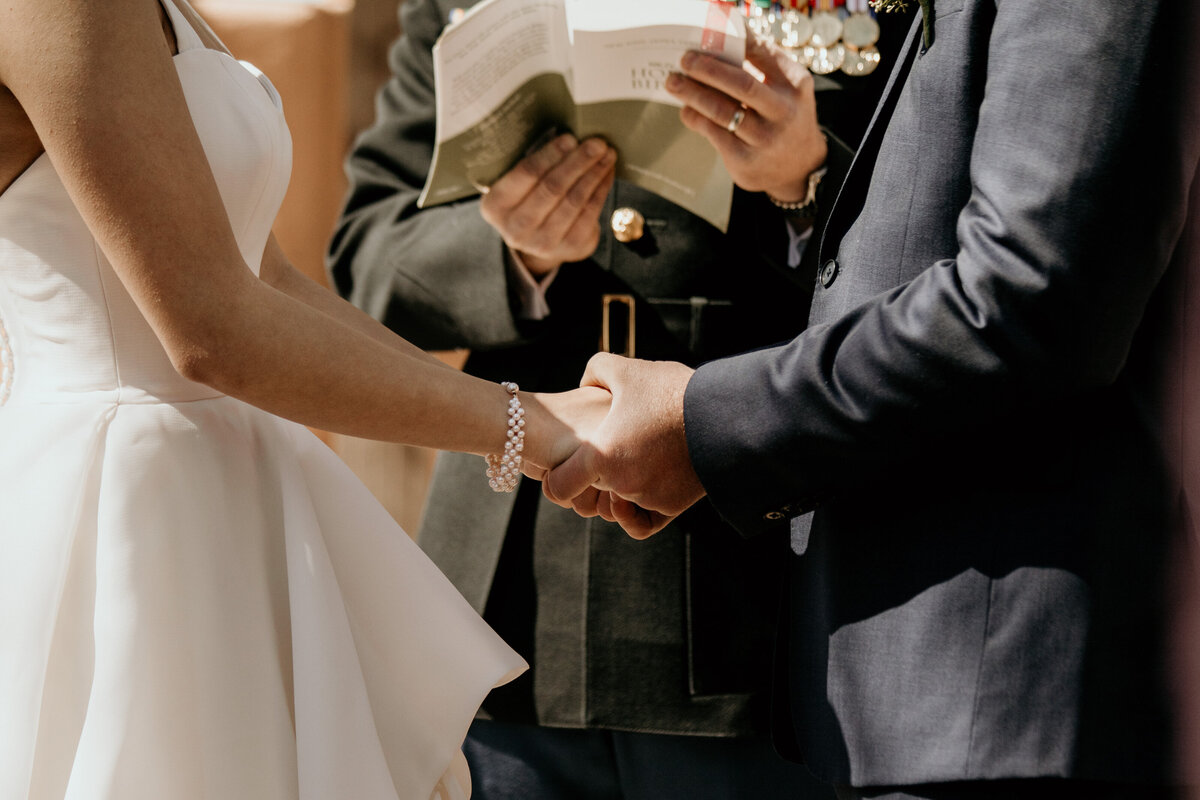 bride and groom holding hands during eremony