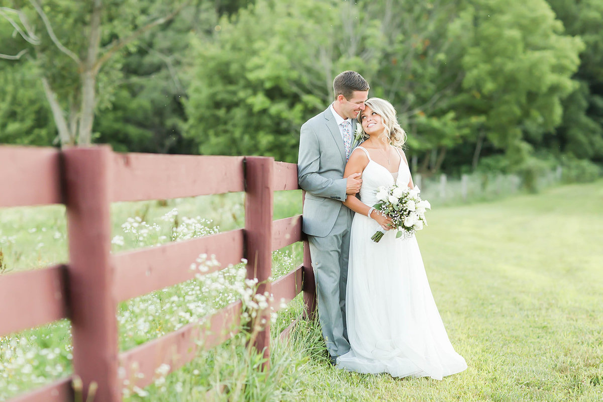 Bride and Groom standing by fence at Peacock Ridge in Ohio