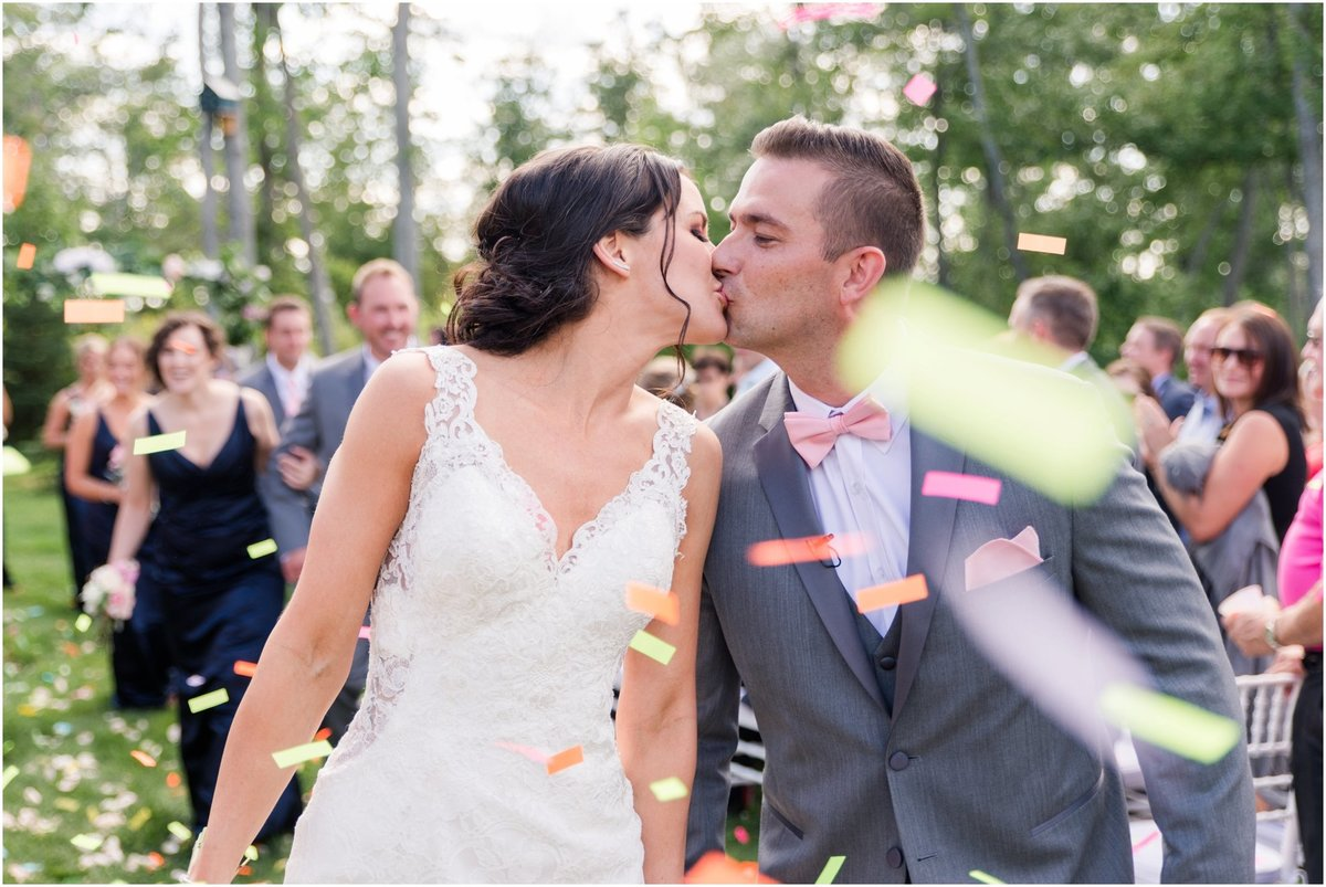 Recessional, bride and groom walking back down the aisle, bride and groom kissing, colourful confetti
