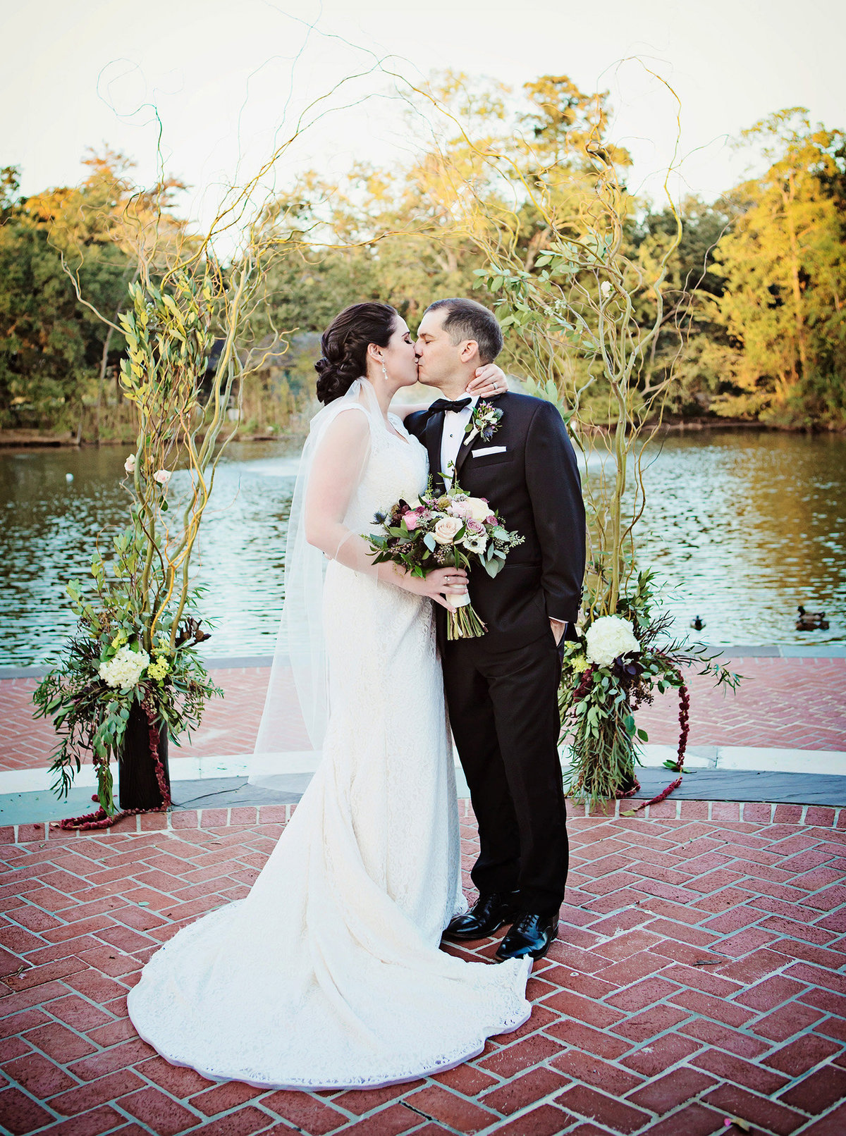 NOLA destination bride and groom kissing in front of pond at Newman Bandstand