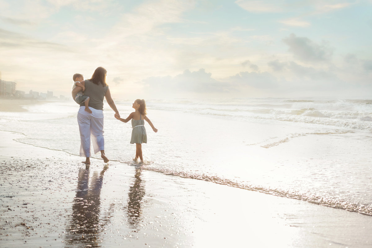 A mother and her two girls walk along the shore during a family photography session