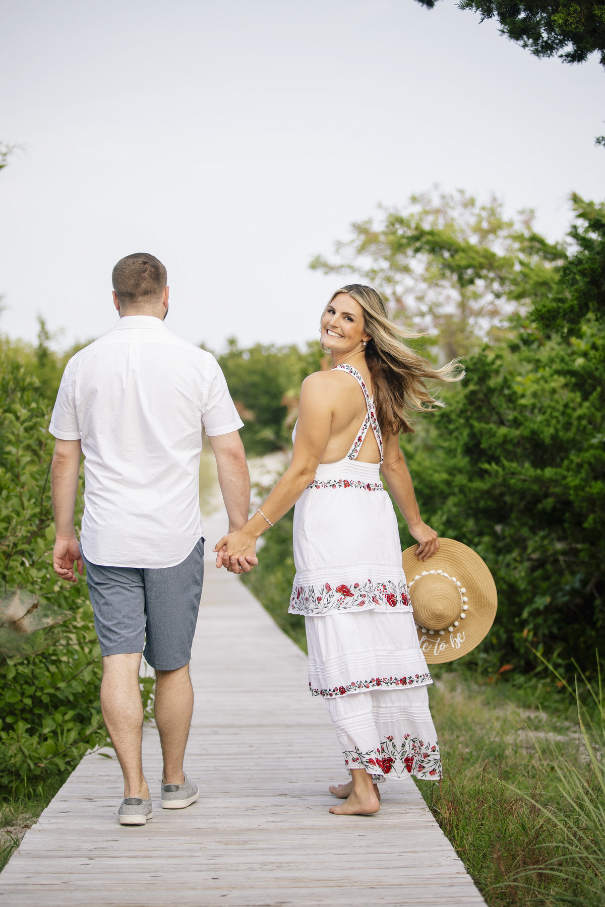 engaged couple walk on path at LBI session