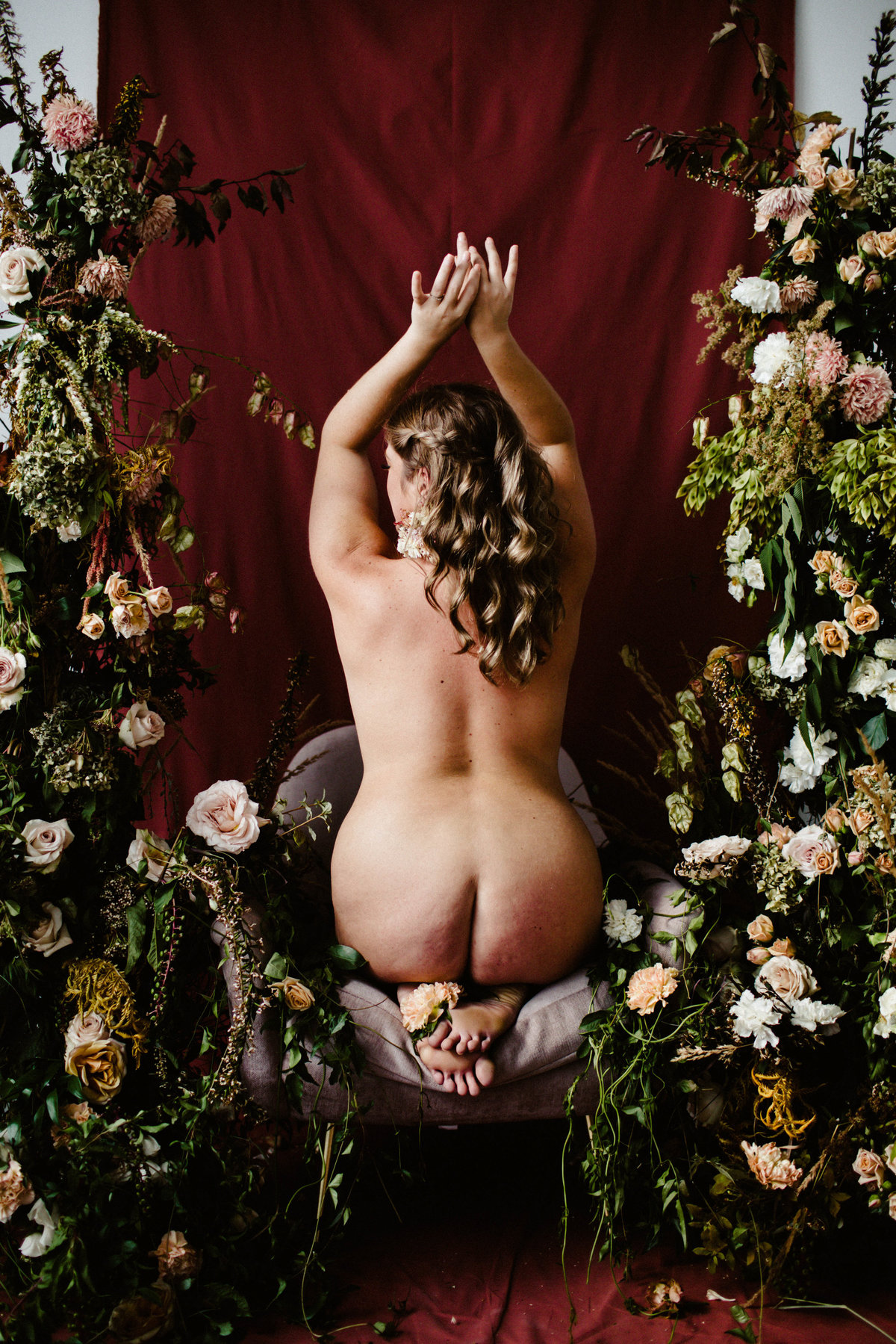 nude woman surrounded by florals and red backdrop