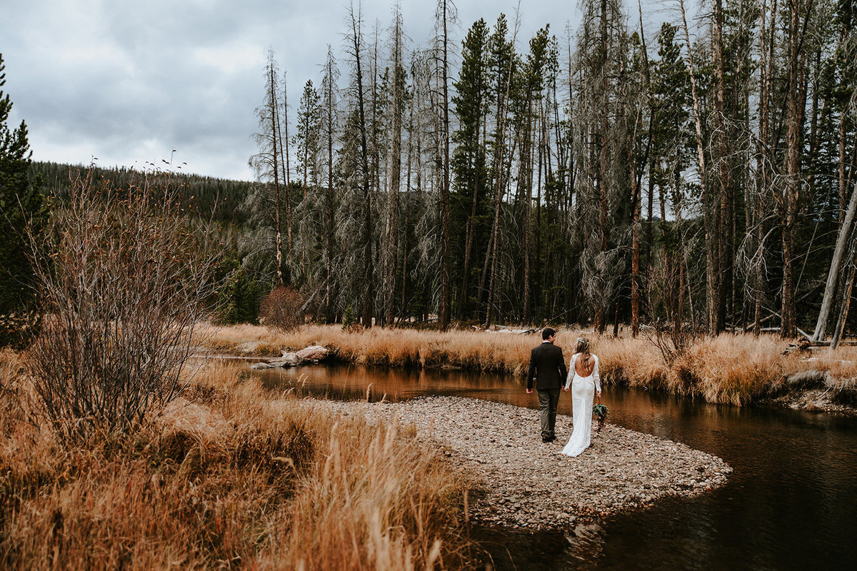 wedding couple walking through fall colors at Grand Lake Colorado