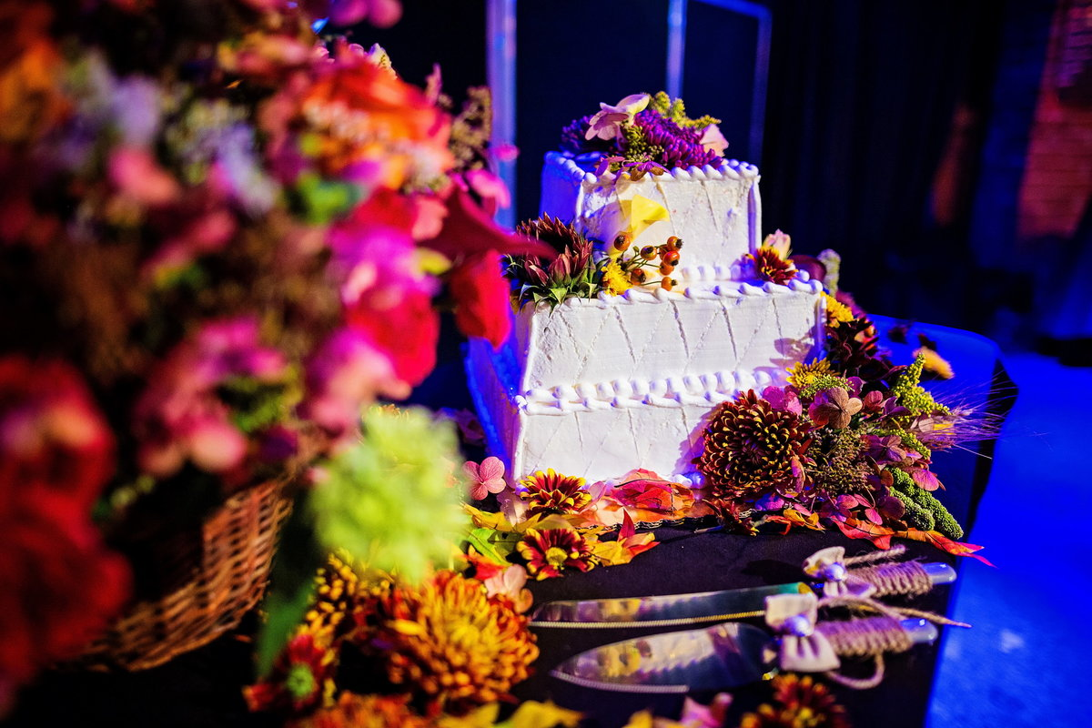 Square tiered wedding cake with colorful florals