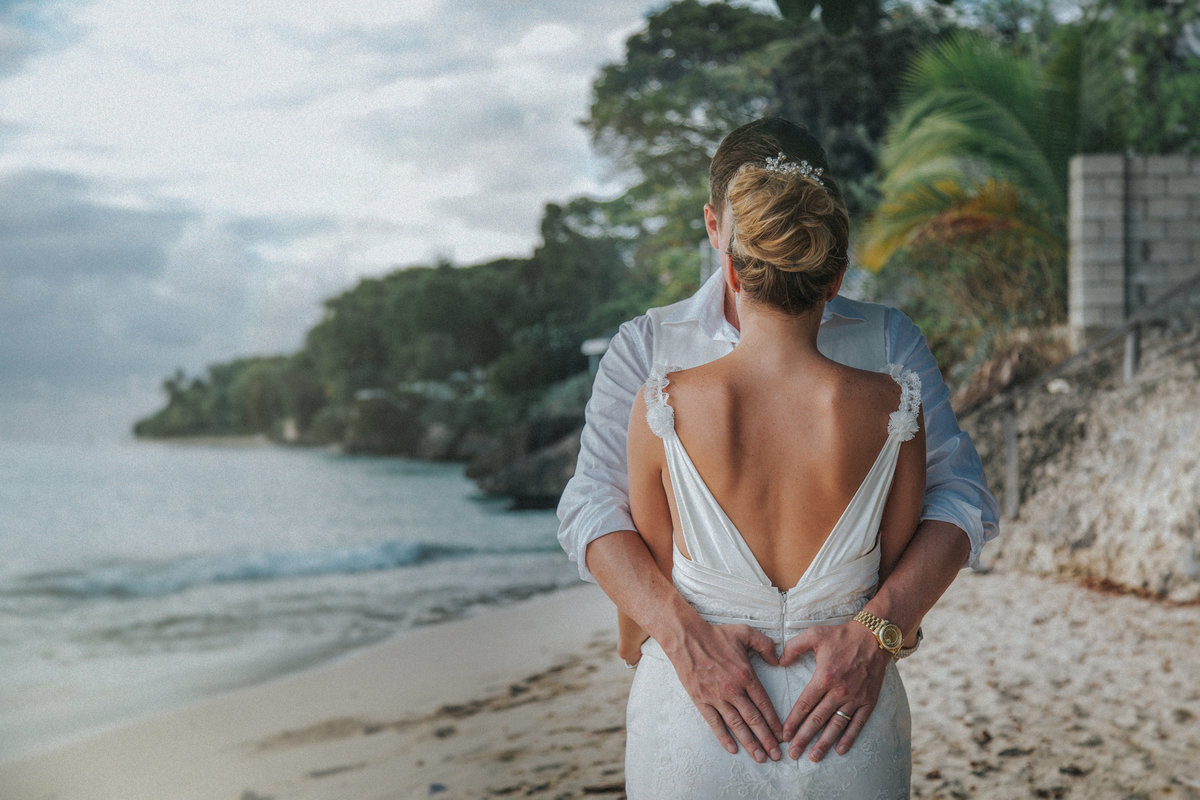 Groom hugging bride forming a heart with his hands on her lower back with a beach as a backdrop by Barbados Wedding Photographer Jono Symonds