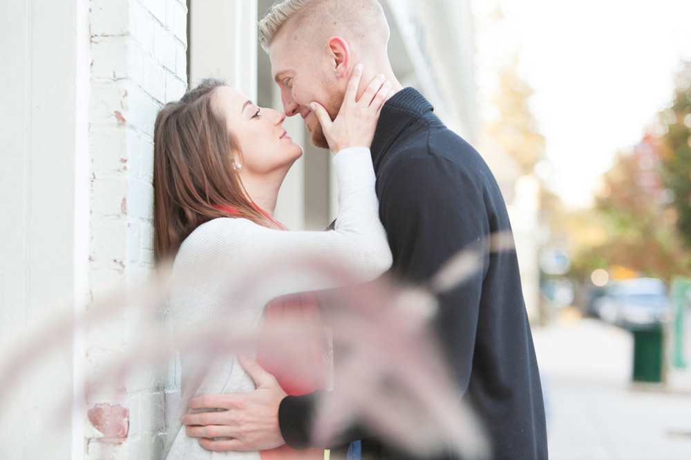 Engaged couple leaning against a wall while kissing