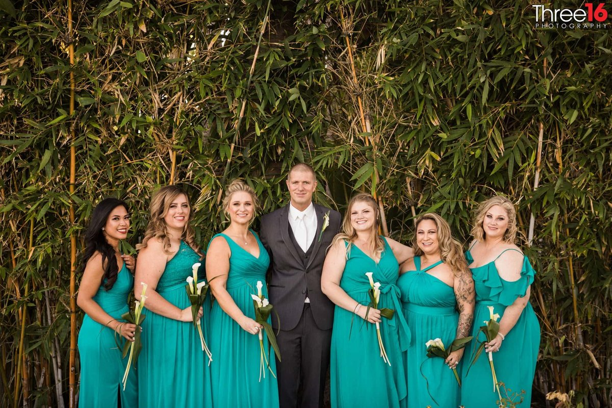 Groom posing with the Bridesmaids