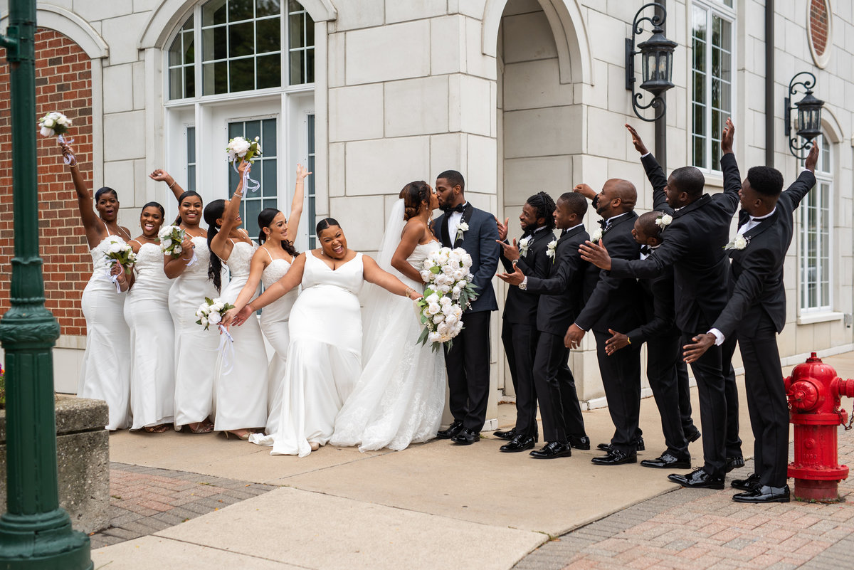 Bride and Groom kissing while their wedding party is cheering and jumping for them.