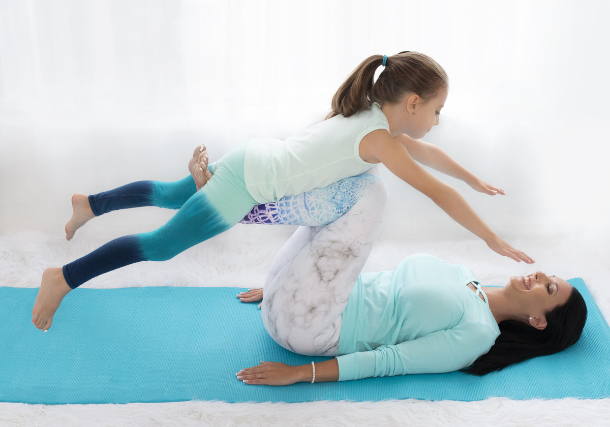mother and  child  doing yoga together on aqua  color  yoga matt family photography