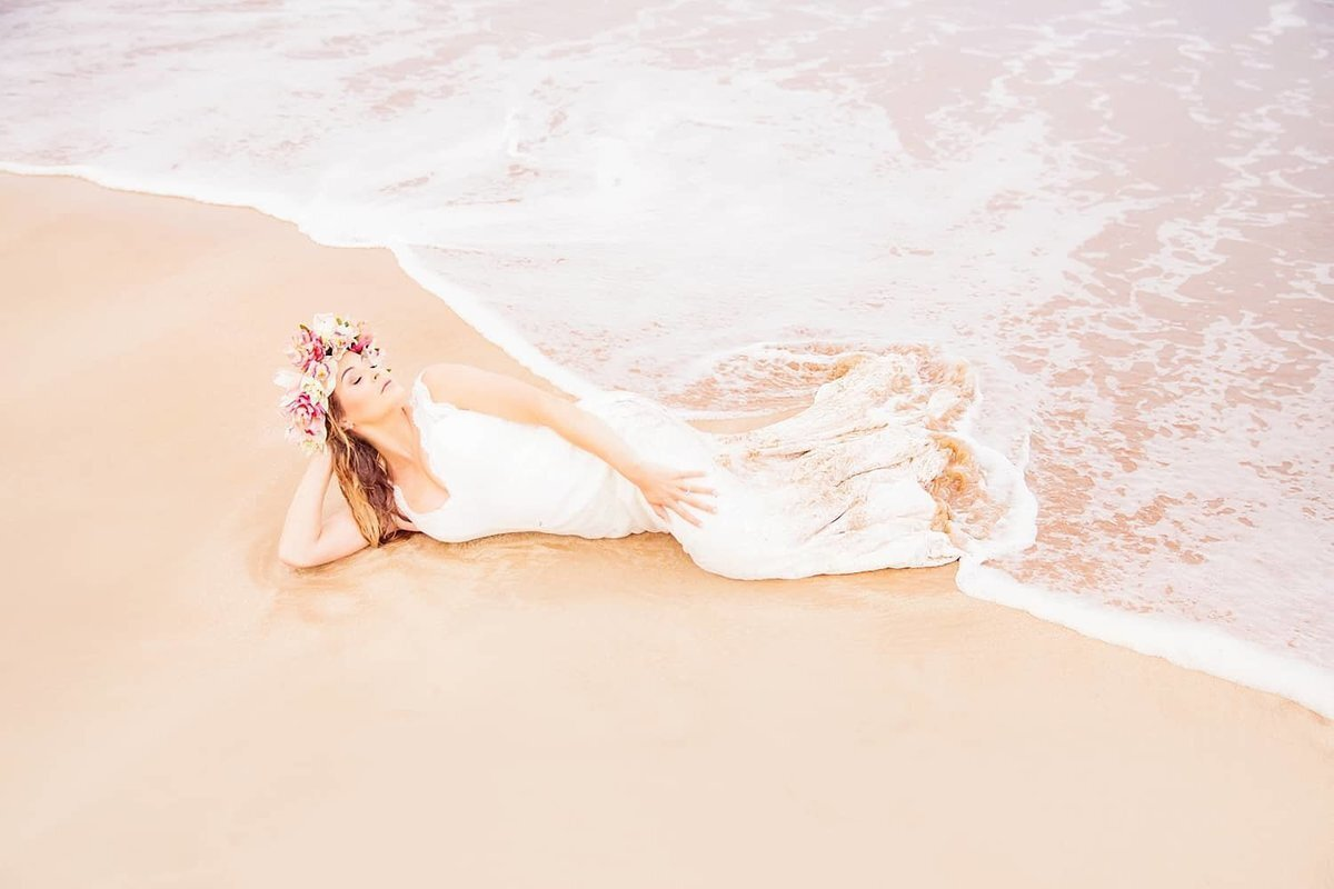 Maui bride posing on the sand as water washes over her wedding dress