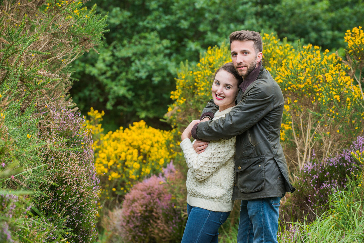 Young couple wearing an aran sweater and wax jacket with denim jeans hugging in a field, surrounded by flowers