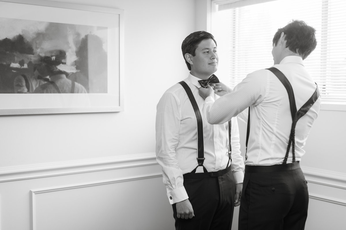 black and white wedding photo of groomsmen helping groom with bow tie at The Garden City Hotel