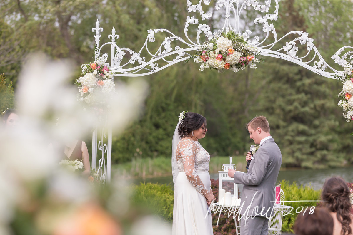 husband reading his bows under flowered arch
