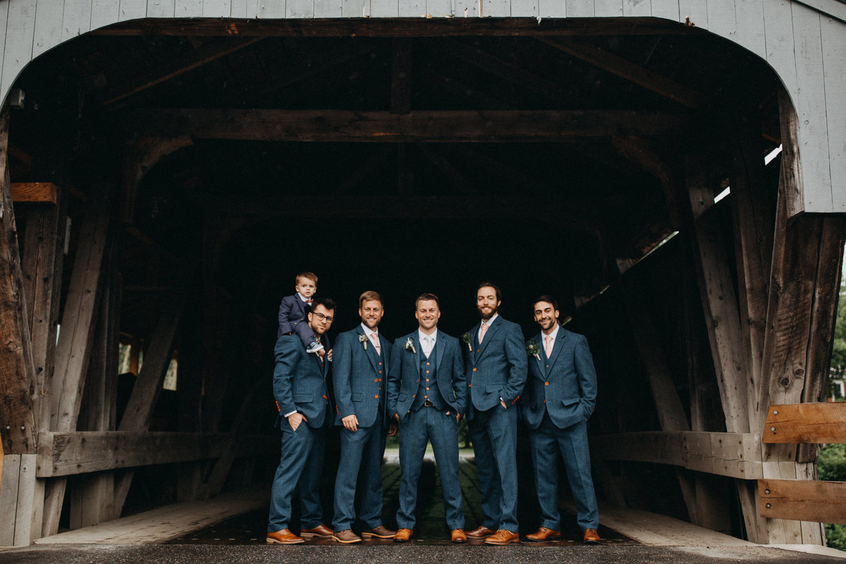 Groom and groomsmen under covered bridge