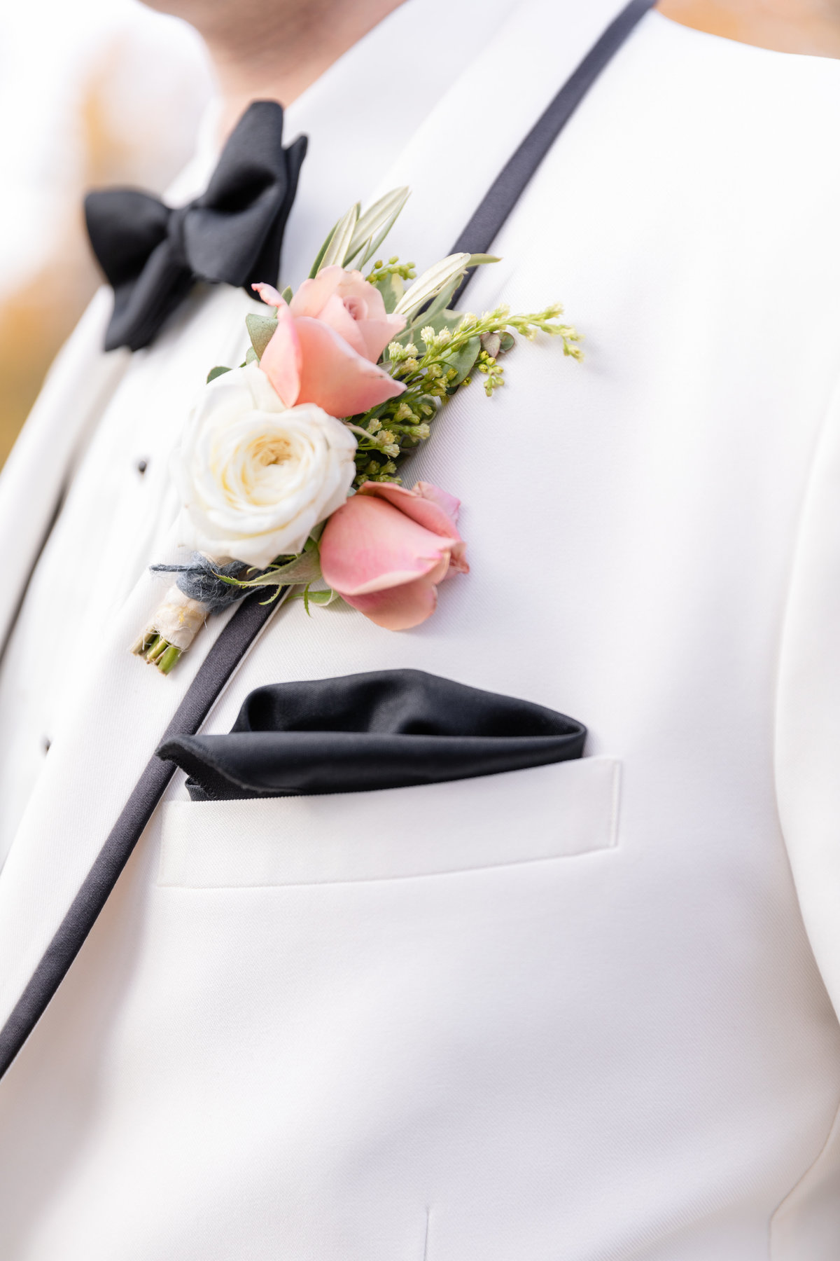 NJ groom in white tuxedo with black details and pink and white corsage