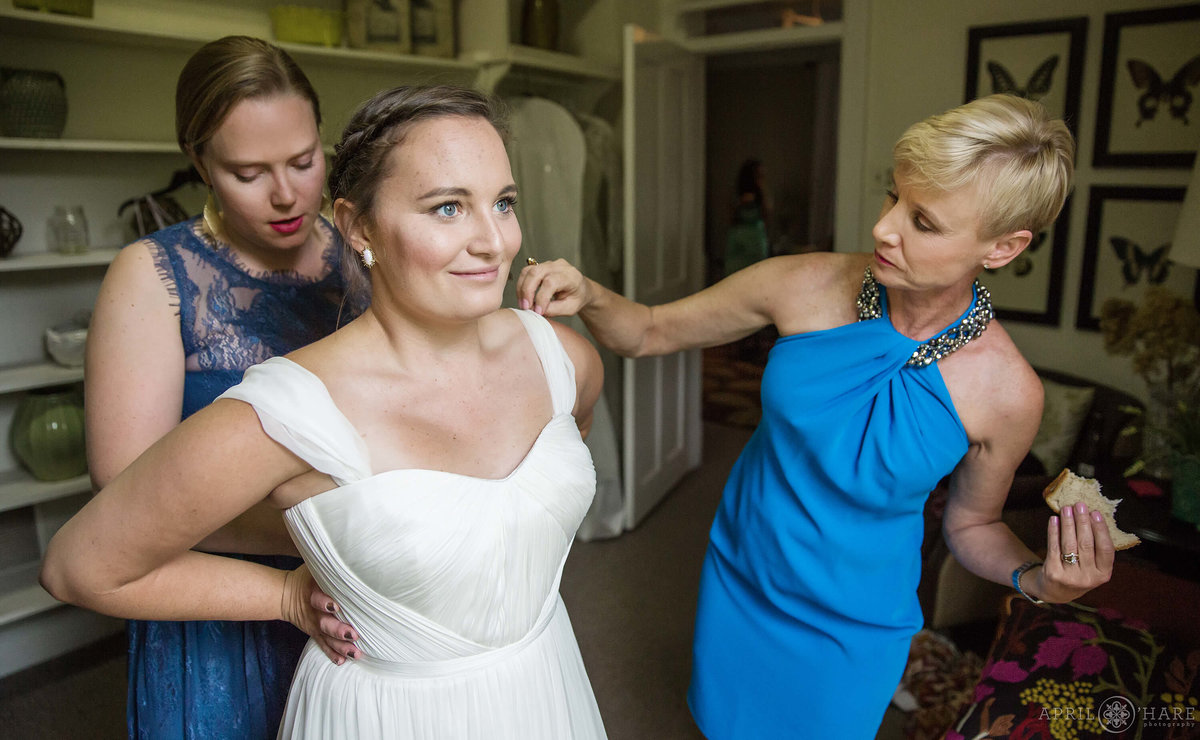 Bride's mom eats a sandwich while helping her daughter get dressed on her wedding day at Chatfield Farms in Colorado