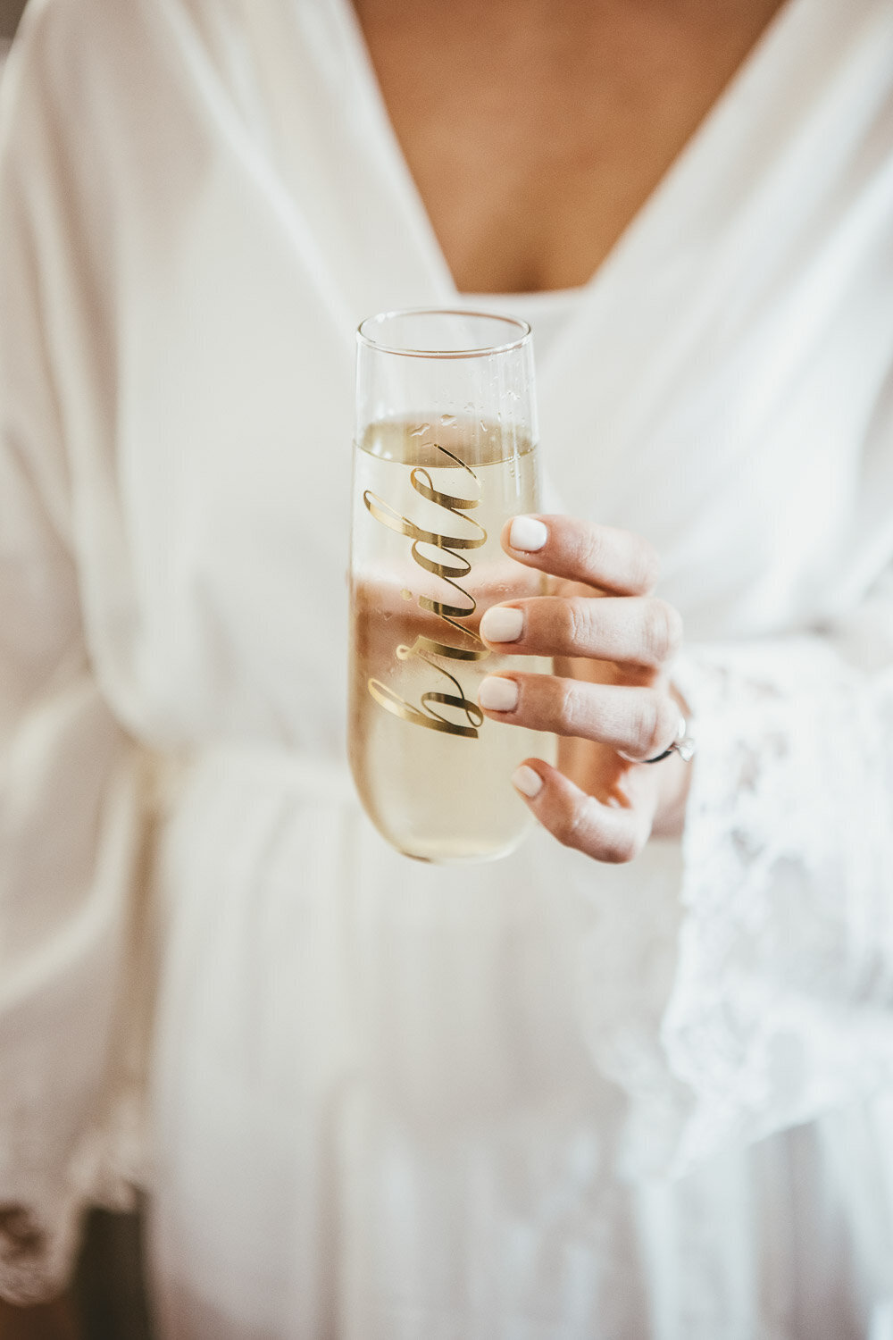 Woman holding glass of champagne with Bride calligraphy on glass