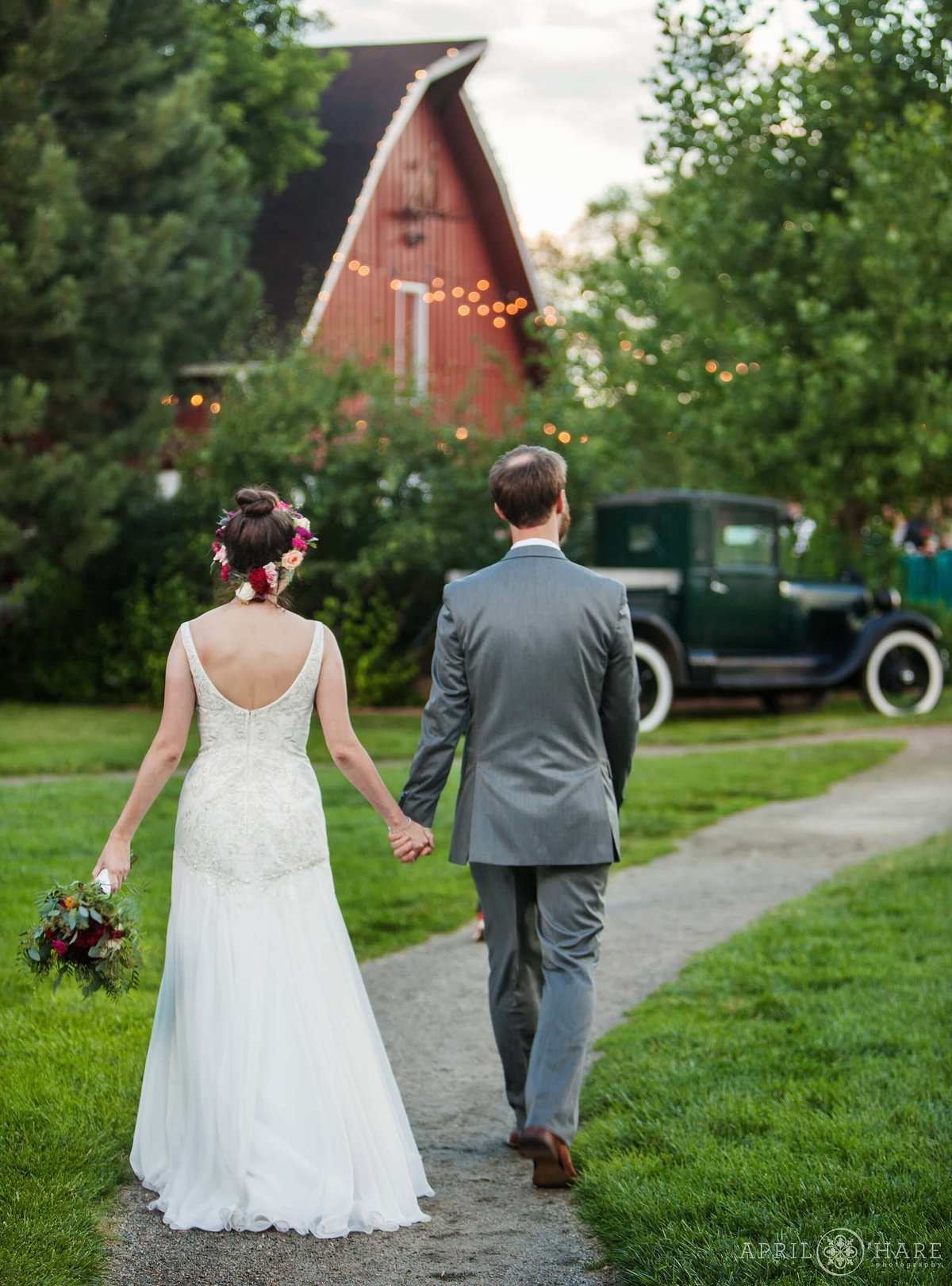 Colorado Wedding Photographer Couples walks to barn reception at Chatfield Farms