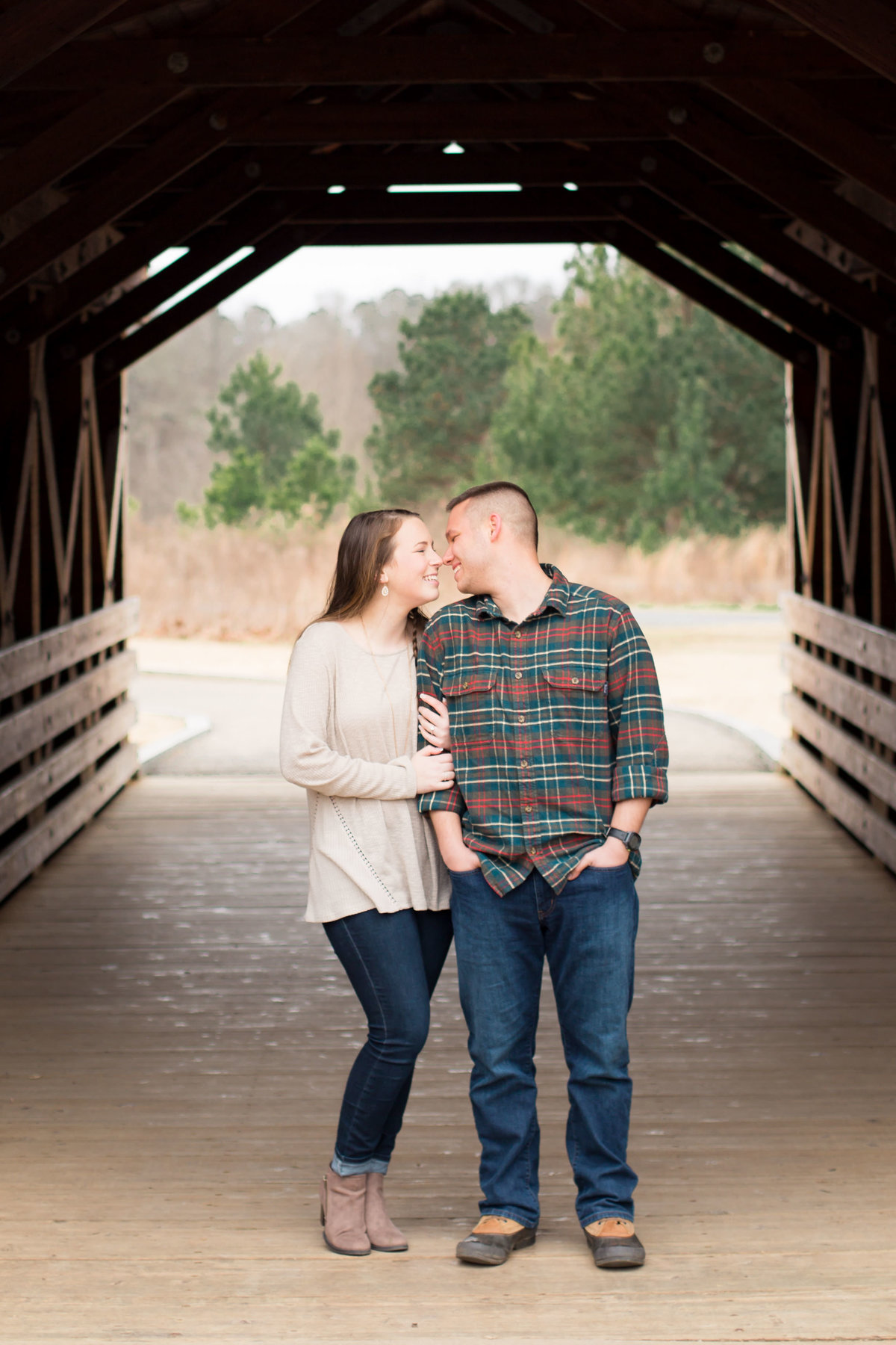 young engaged couple under rustic covered bridge