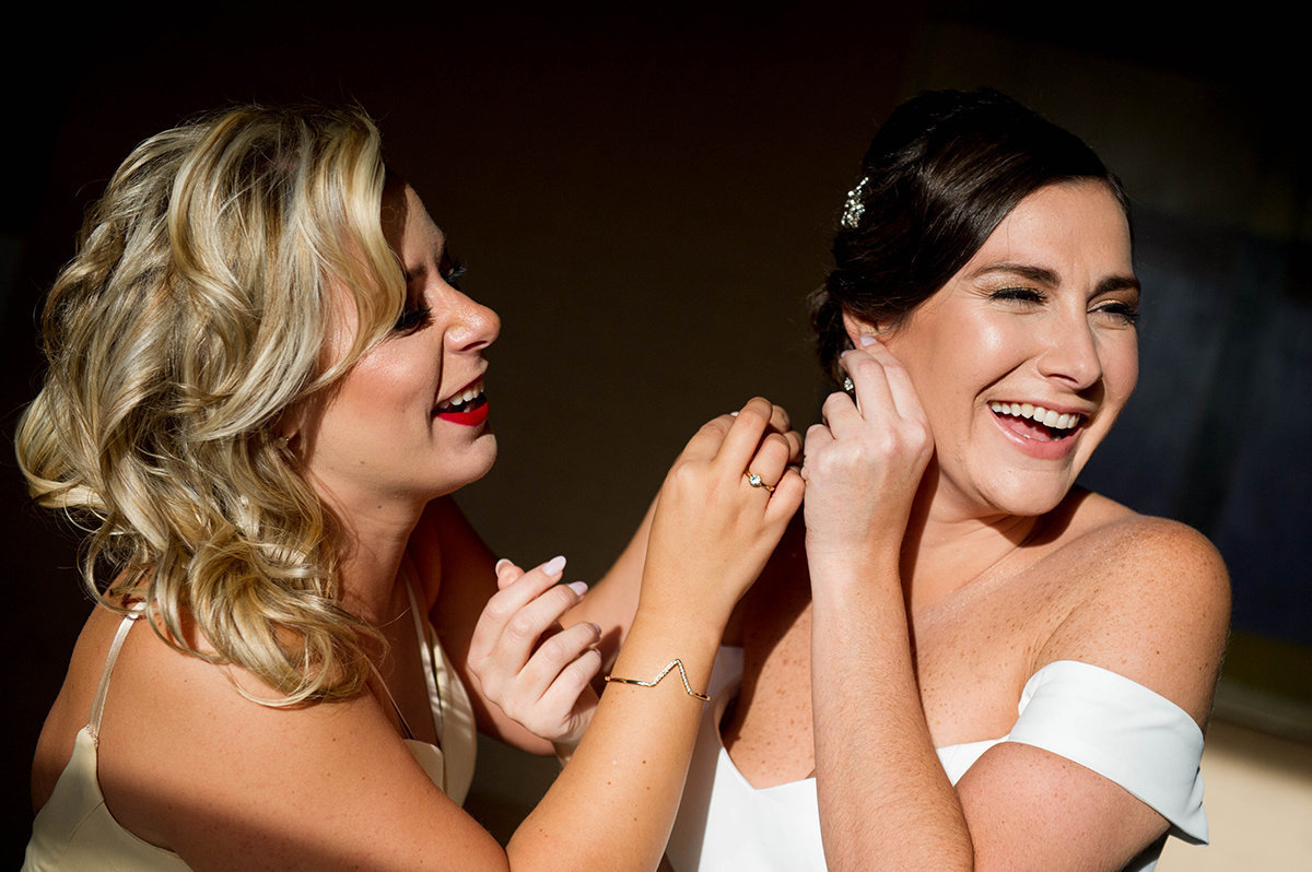 bride gets help putting earrings on