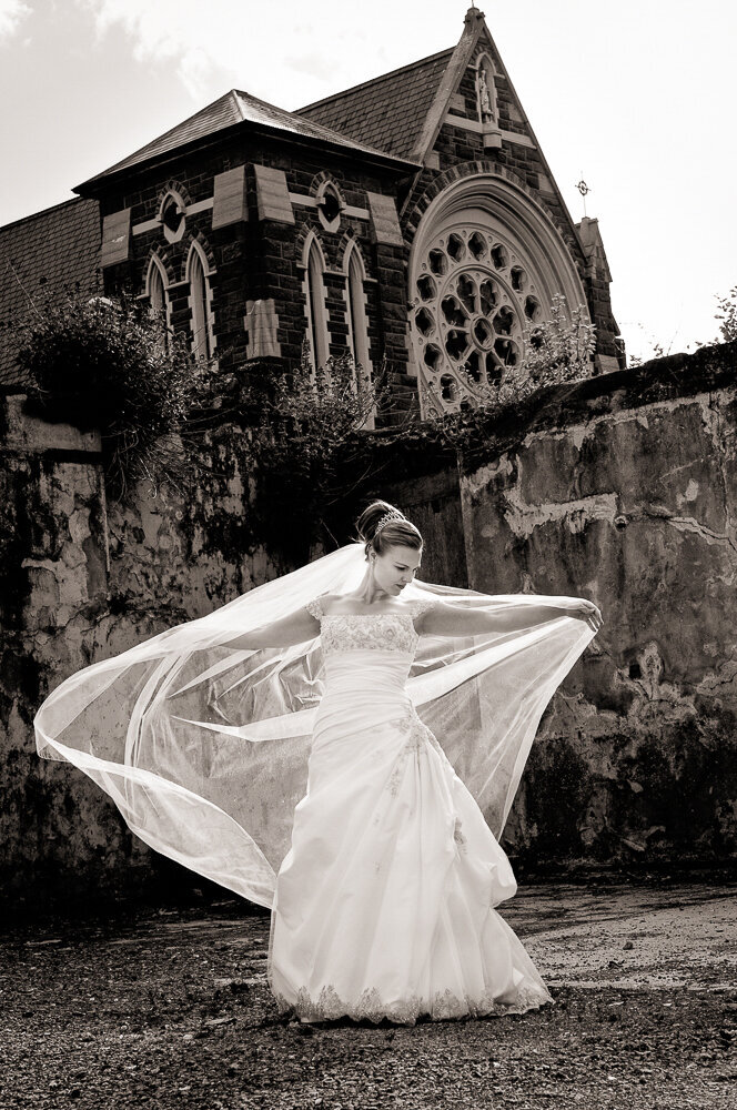 bride wearing a trumpet style wedding dress, holding a long veil blowing in the wind in front of the church
