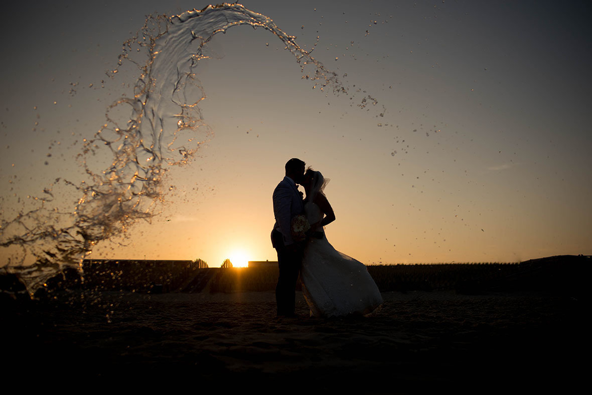 wave of water and bride and groom with sunset