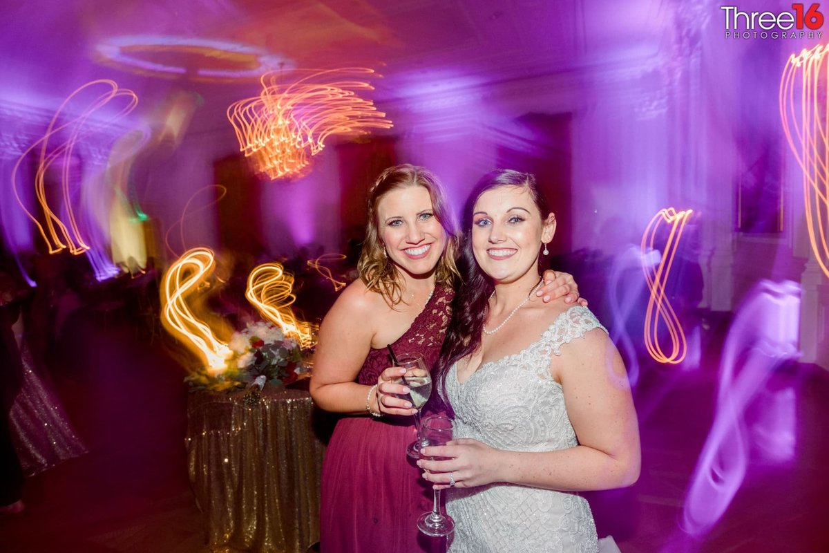 Bride and Bridesmaid are all smiles at the reception