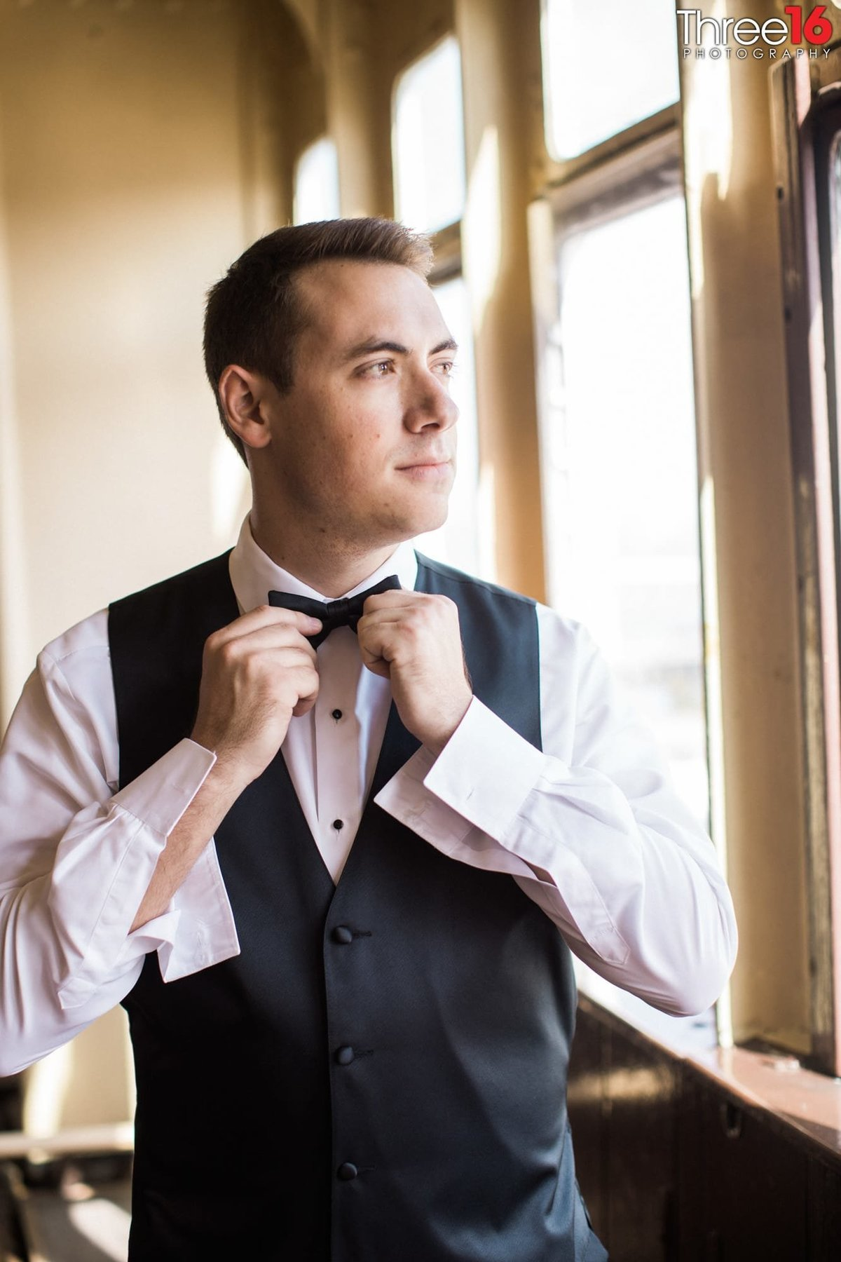 Groom straightening his bow tie before the ceremony
