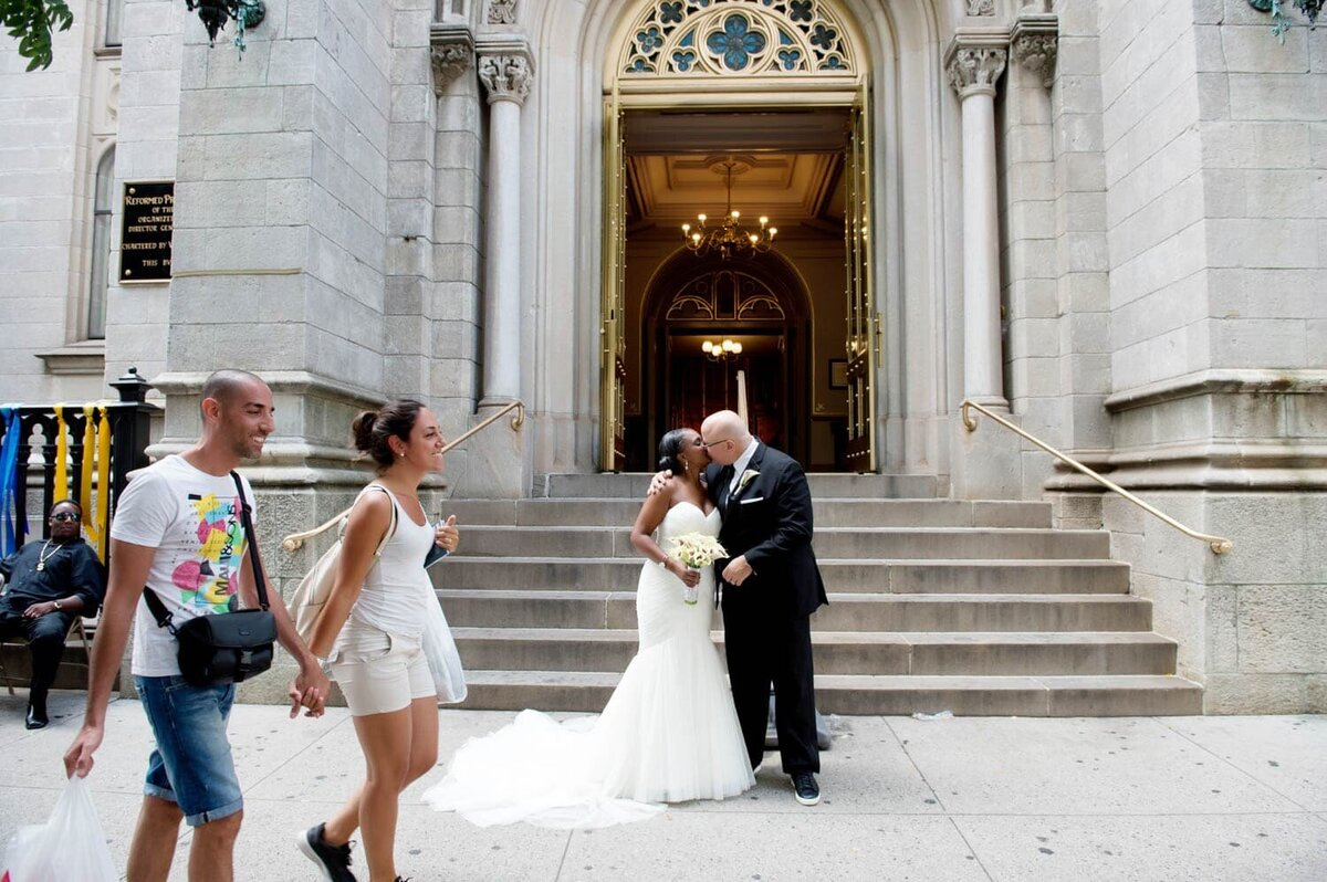 a bride and groom kiss in nyc as passerbys look on and walk past