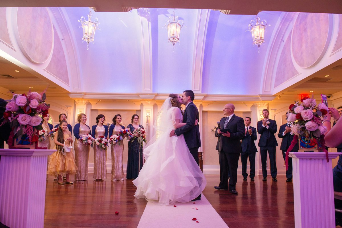 Bride and groom's first kiss at the Chapel at Watermill Caterers