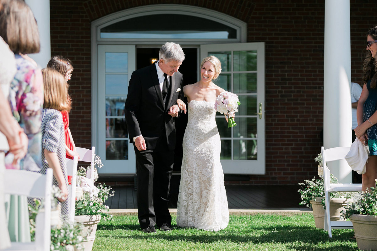 The bride walks down the aisle with her father and laughs in Bar Harbor Maine wedding