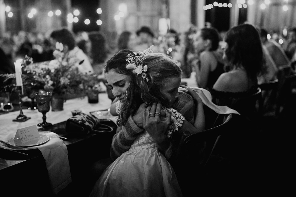 A woman and young girl hugging at a wedding reception.