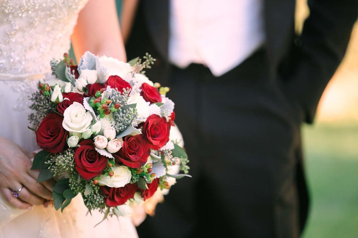 Bride holding a white and red rose bouquet at The Mansion at Oyster Bay