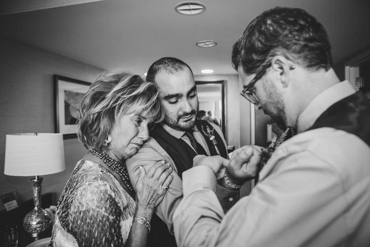 Brother putting watch on groom and mom crying