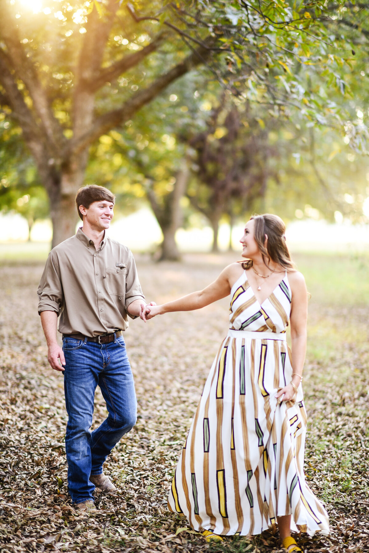 Beautiful Mississippi Engagement Photography: Couple walks hand-in-hand in a sunlit Mississippi delta pecan orchard