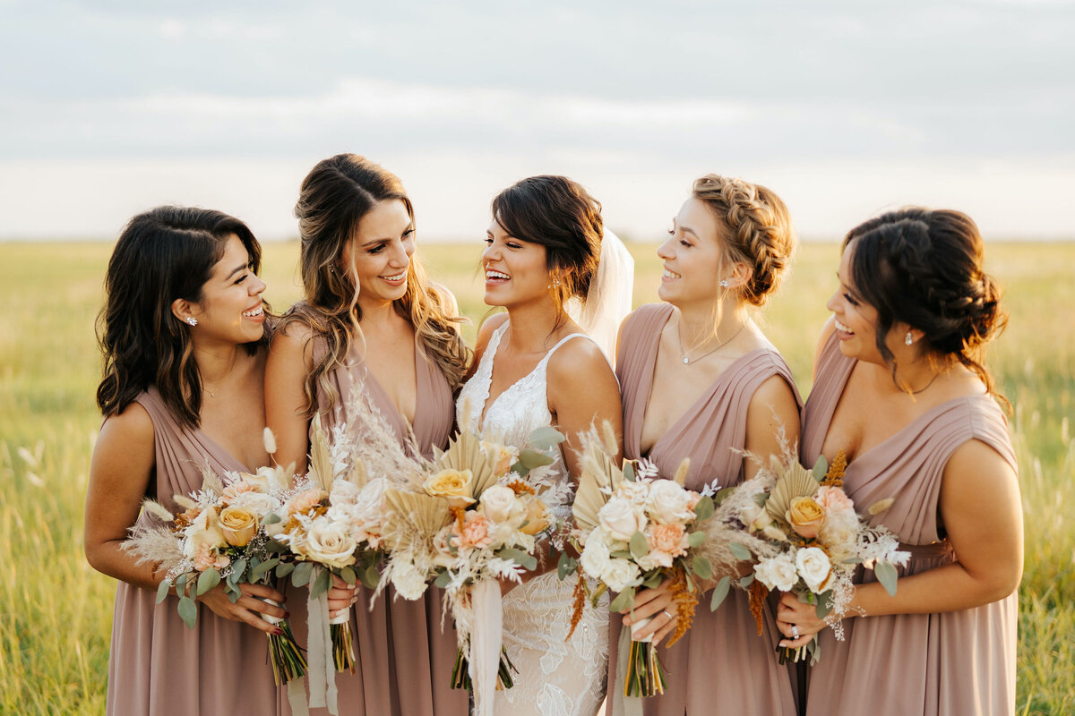 Bride and bridesmaids in dusty rose dresses with orange and white flowers