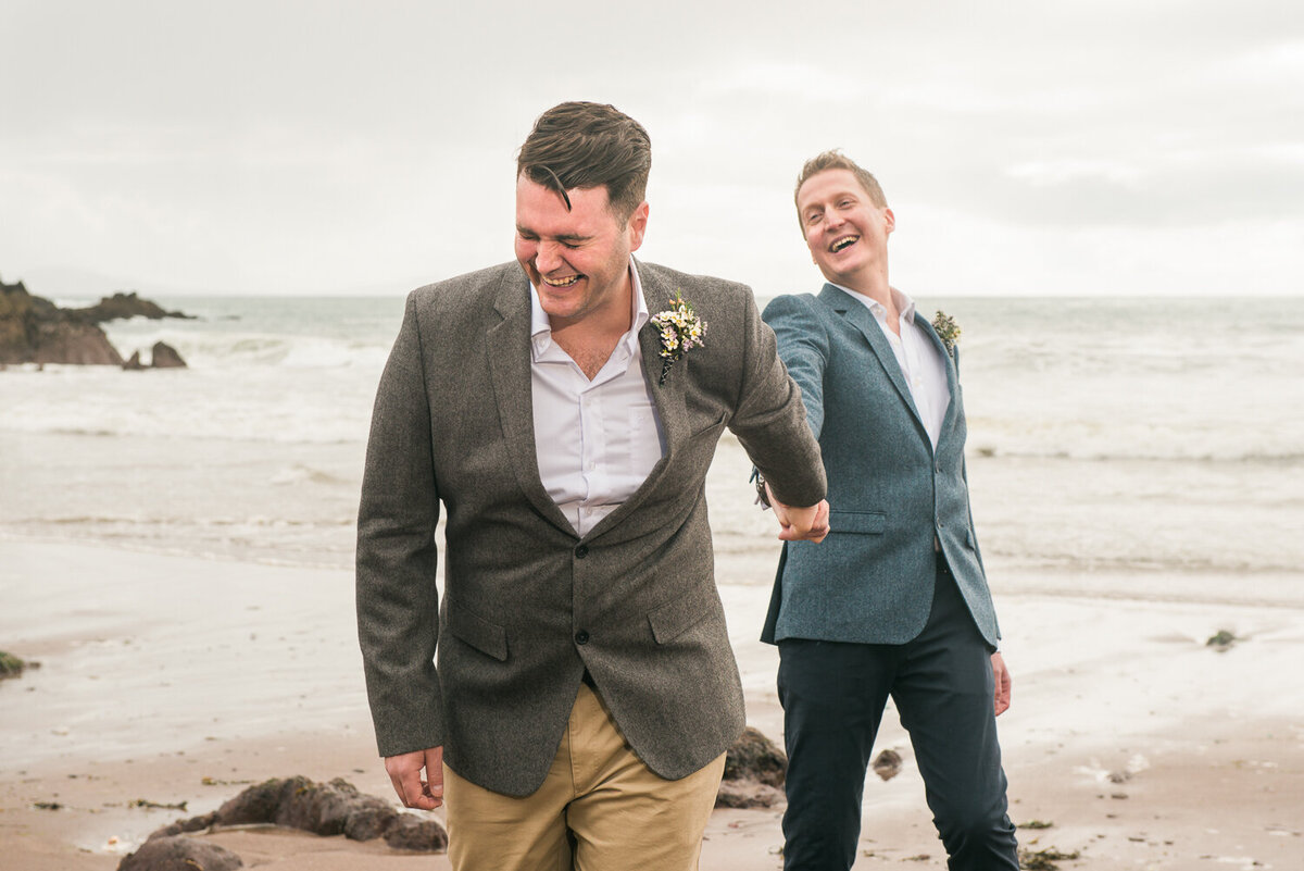 Gay male wedding couple holding hands and laughing on beach